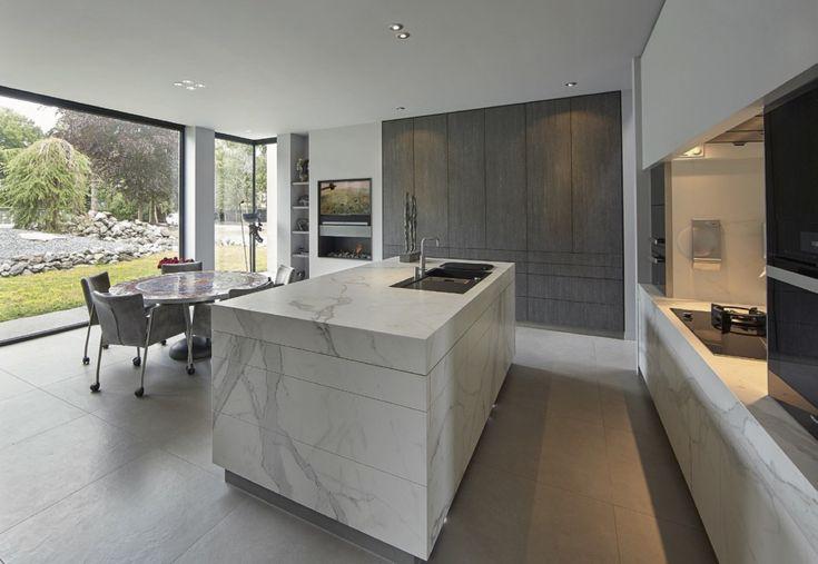 Het aanrechtdeel met de kookplaat en de ovens L+R + de strakke plaat met de afzuigkap erachter, mooi! daarnaast het aanrecht door laten lopen om de hoek met de spoelbakken erin