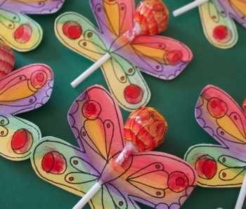 Con una cartulina que decoraremos a nuestro gusto y le daremos una forma que queramos como por ejemplo una mariposa, realizaremos dos cortes en el centro por donde pasaremos el palo del chupa-chups o piruleta.
