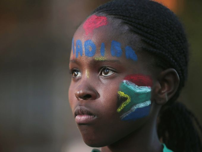A young girl has the tribal name of Nelson Mandela, Madiba, painted on her face outside the Mediclinic Heart Hospital.  Christopher Furlong, Getty Images
