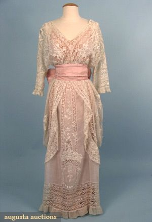 """LACE HOBBLE-STYLE TEA GOWN, c. 1913 1-piece fashioned from various laces including Val, torchon, & embroidered net, the skirt panels embroidered w/ flower baskets, wide pink brocade silk sash, B 42"""", W 29"""", L 54"""""""