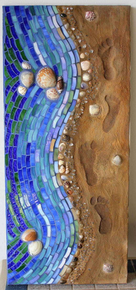 Diese ruhigen und einzigartigen Mischtechnik-Mosaik verfügt über eine Küstenlinie mit Fußspuren im Sand. Das Wasser wurde mit einer Vielzahl von Farben und Texturen der Glasmalerei, einschließlich einige schillernde Stücke erstellt. Die Fugenmasse verwendet für das Wasser ist blau gefärbt.  Die Küstenlinie enthält, Kieselsteine, Muscheln und kleine Glas-Nuggets mit einer leichten braun Fugenmörtel Sand zu imitieren. Der Sand selbst wurde mit einem Produkt Zement-Typ und die Spuren in den…