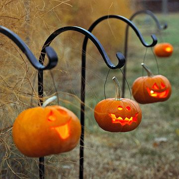Hangin' Around  Bend thick wire (or clothes hangers) into handles and use them to hang small jack-o'-lanterns on shepherd's hooks along an outdoor path.
