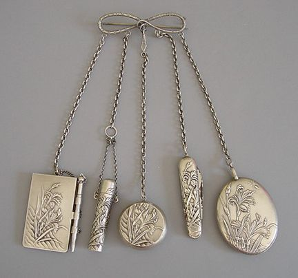 CHATELAINE sterling chatelaine. Suspended from a snake in the symbol of infinite love 2-1/2 brooch are: a 2 notepad and pencil; 2 pocket knife; 3-7/8 perfume with tiny glass stopper; 1-1/8 powder and puff; 2 mirror and photo oval, all with matching motif.