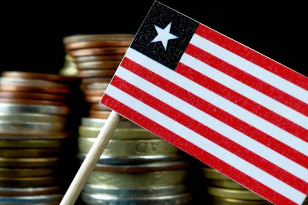 liberia flag waving with stack of money coins macro