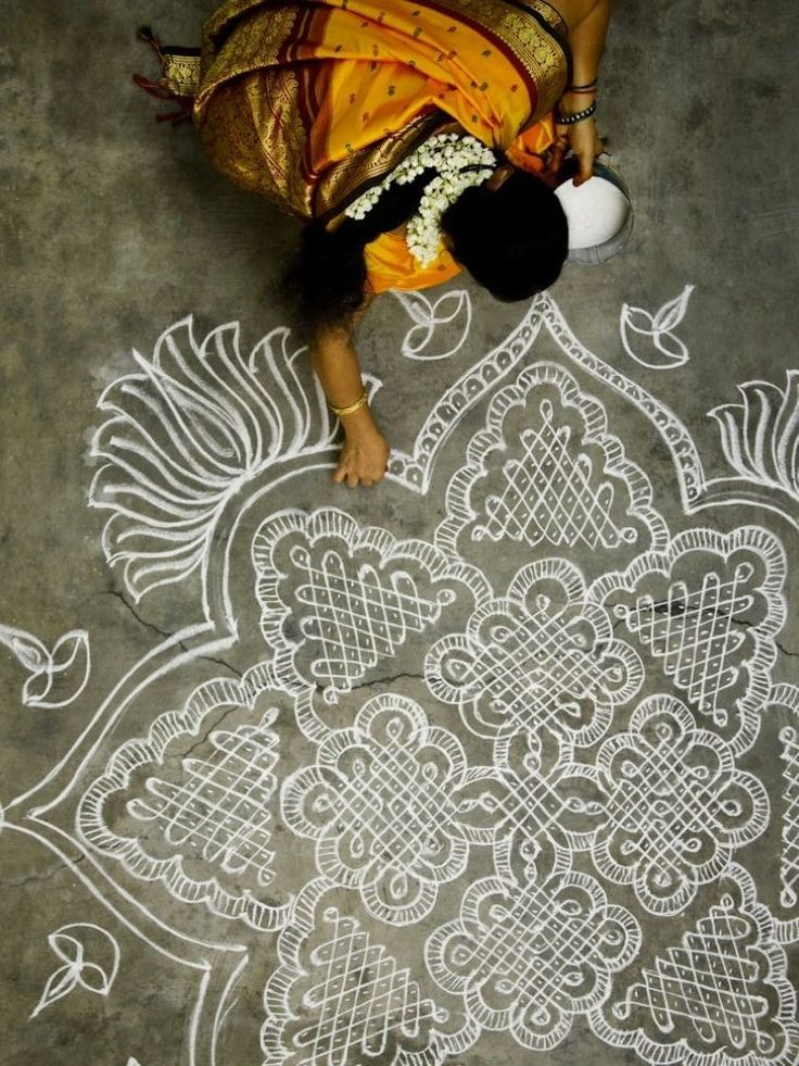 "Woman making a kolam in south India: ""Especially during the harvest season, you'll see many women making kolams outside their homes in the morning. Kolams are beautiful patterns made from rice flour. Besides for decoration purposes it was a way to feed birds and critters. A way to honor that all life is sacred and a tribute to harmonious co-existence."""