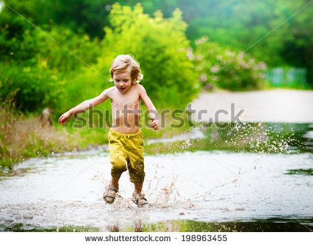 Little boy runs through a puddle. summer outdoor - stock photo