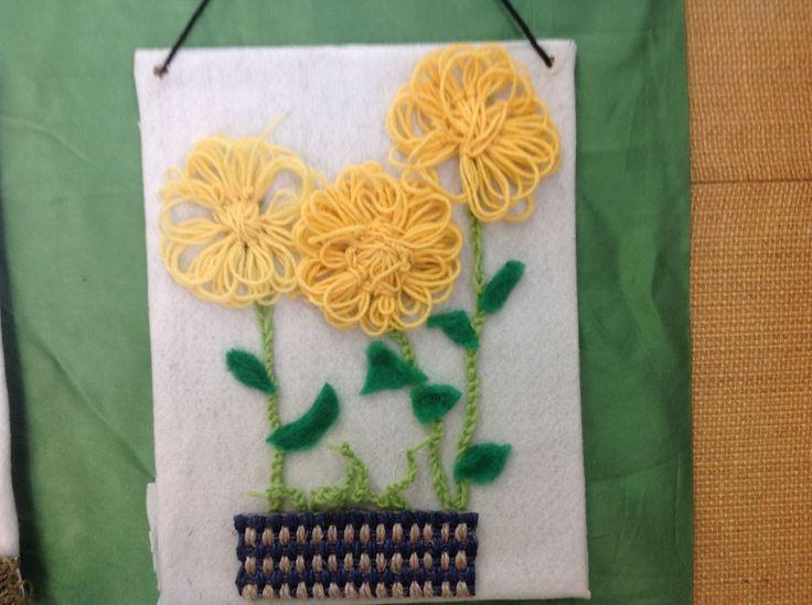 """""""Kukkataulu"""" (4.lk) Kukat tehty villalangasta, kukkien varret virkattu ja lehdet huovutettu. Kukkaruukku reunustettu pykäpistoilla. (Alakoulun aarreaitta FB -sivustosta / Peiposjärven koulu)"""