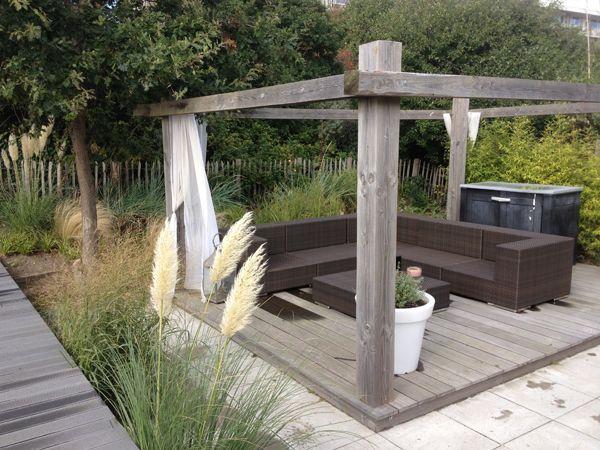 Mooi, open terras omringd door een haag van siergrassen.