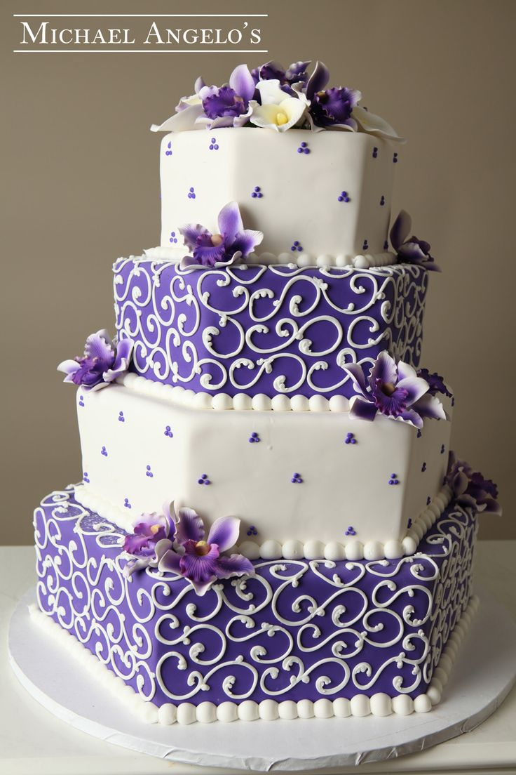 Hexagon & Swirls #8Classic This is a three-tier fonant cake design.  The fondant is smoothed out to perfection, including the corners to really bring out the hexagon shape.  The royal purple fondant was added to match the theme of the wedding.  The gum paste flowers bring the cake to life.