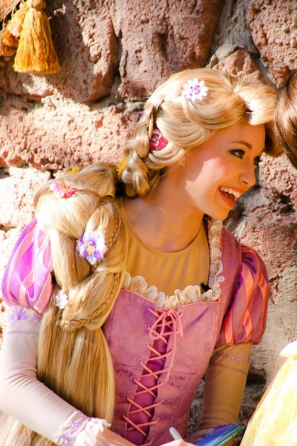 I am trying to figure out why the rapunzel in Disneyland and Disney world has her long blonde hair when she is supposed to have her short brown hair.....