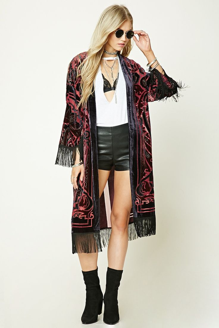 A woven kimono featuring an open front, dropped shoulders, long kimono sleeves, fringed trim, and a velvet applique in geo, paisley, and stripe patterns.