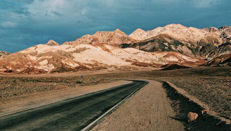 A narrow asphalt road through the arid Death Valley