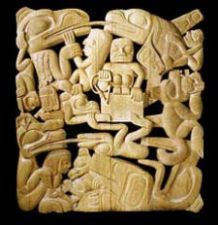 Carved cedar screen showing prominent beings from Haida stories.