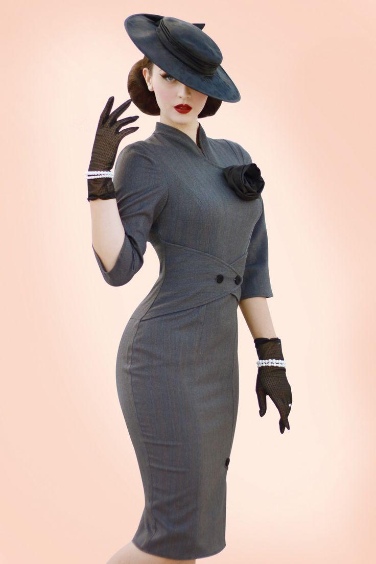 """De50s Idda Herringbone Wiggle Dress in Greyvan Miss Candyfloss geeft je een ultiem zandloper figuur!  Deze jurk is geïnspireerd op de """"wiggle dresses"""" uit de jaren 50 en ontworpen door niemand minder dan Idda Van Munster. Klassiek, elegant en door zijn fantastische vrouwelijke snit ook sexy, oh la la! Het aansluitende lijfje heeft 3/4 mouwtjes, een mooi opstaand kraagje met een overslag detail en een prachtige zwarte vaste taffeta roos. De taille wordt perfect geaccentueerd ..."""