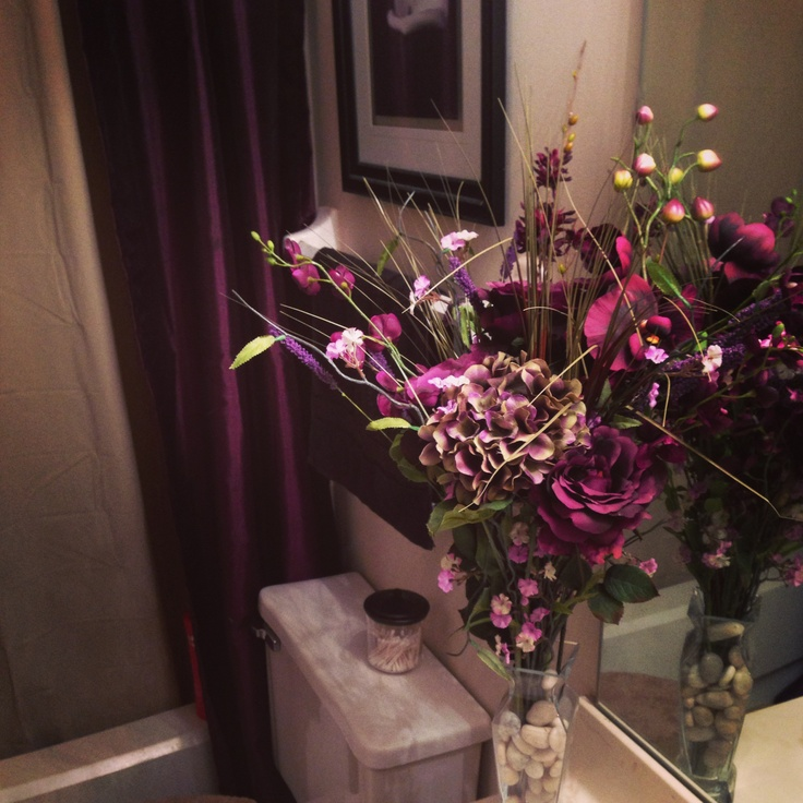 Deep purple shower curtains and purple flower bouquet for a small bathroom.
