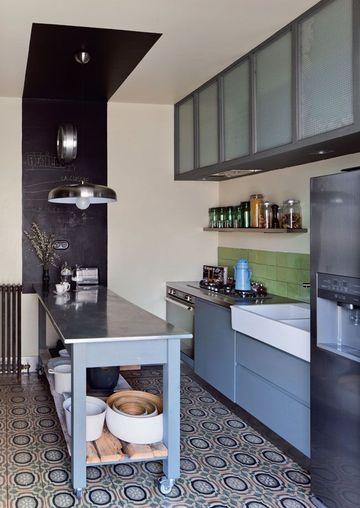 Fidèle a l'esprit rétro, la cuisine est elle aussi baignée par cette ambiance. Des carreaux de ciment au sol, un plan de travail avec un plateau en zinc et des roulettes, un bleu pastel. Pour délimiter l'espace dédié à la préparation et créer un effet de perspective ingénieux, une bande noire a été peinte au mur, débordant jusqu'au plafond pour souligner le plan de travail.