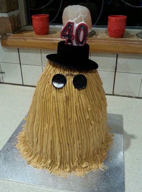 """""""Cousin it"""" Adams family birthday cake. Buttercream frosting over red velvet cake, ran a fork through the frosting for the hair effect. Hat and specs from a craft store"""