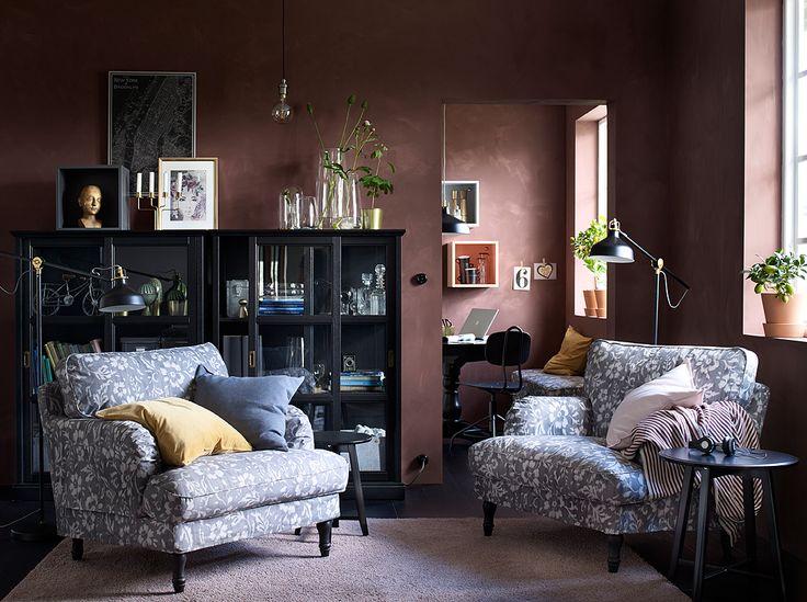 Čierno-hnedá obývacia izba s dvoma veľkými kreslami so sivým a bielym poťahom s kvetinovým vzorom.