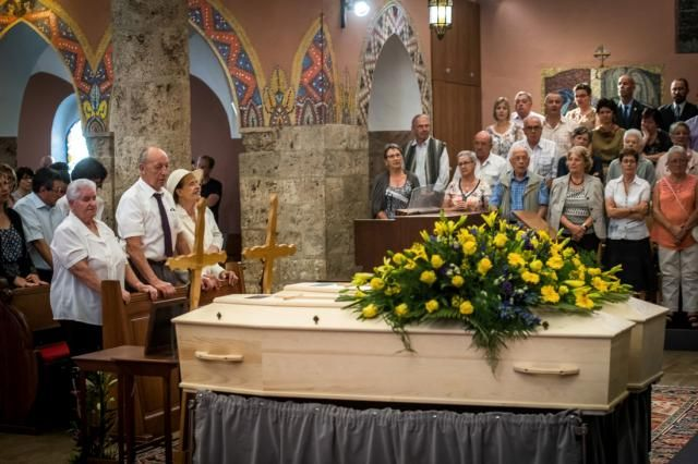 The late couple's daughter, Marcelline Udry, seen third from left, attends her parents' funeral ceremony in Saviese, Switzerland, on Saturday. (OLIVIER MAIRE via Getty Images)