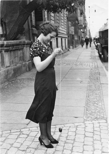 A woman yo-yoing on the street, 1930s.