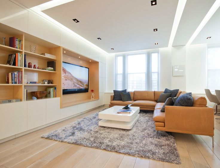Idea soggiorno moderno in colori dominanti bianco e marrone. Pavimento in legno così come l'interno della libreria. Soffitto in cartongesso con particolare illuminazione