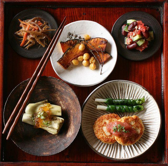 Japanese Dishes. Tofu hambagu with ume sauce, pickled long green onion, steamed eggplant, sauteed pumpkin & chickpea, tomato & cucumber salad, and kinpira salad