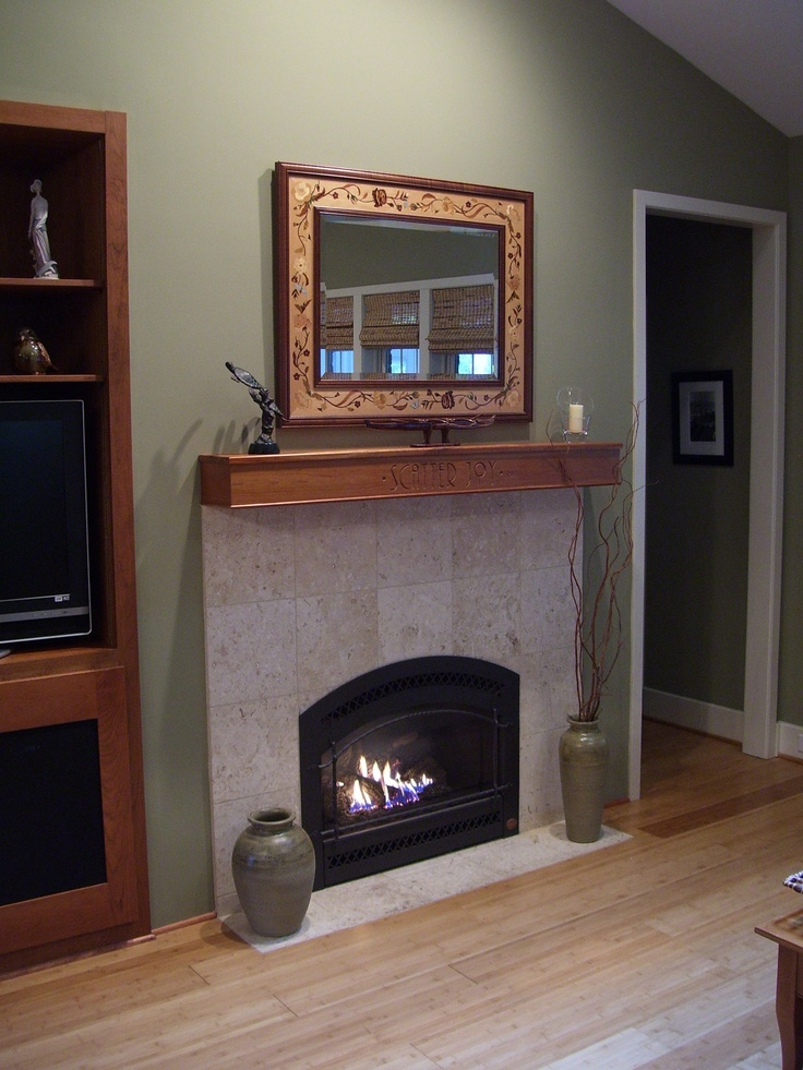 """an arched Fireplace Xtrordinair, with a hand-hammered """"artisan"""" iron face, finished simply, with a motto laser-engraved on the mantel shelf:    * SCATTER JOY *"""