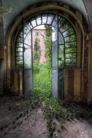 Arched glass opens to the garden of abandoned castle. by Hercio Dias