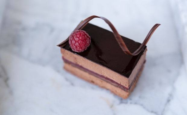 Chocolate mousse layer cake with chocolate sponge and raspberry jelly.