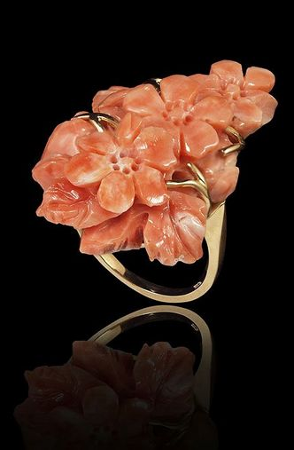 HAND CARVED NATURAL CORAL RING: A three dimensional floral carved coral, approx. 35 mm, in a 14K yellow gold ring.