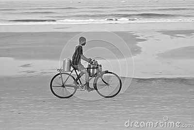 A young tea seller on a bicycle in a beach in North Goa, shot in black and white.
