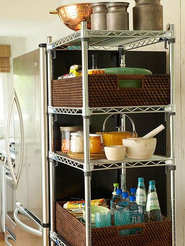 Unfitted storage units are a savvy solution for boosting your kitchen's storage real estate. This sturdy metal shelving unit, squeezed in next to the refrigerator, is outfitted with baskets to hold baking supplies and bottled drinks.