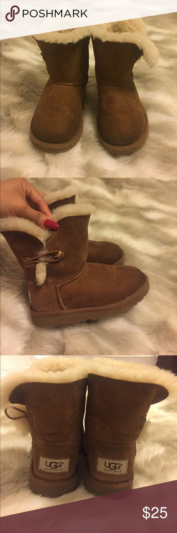 Girls Ugg Boots in Camel Worn condition but still pretty good shape! Cute girls Ugg boots! One button missing as pictured and the other almost gone. I am sure you can sew a new one on for the band to clasp onto very easily. UGG Shoes Boots