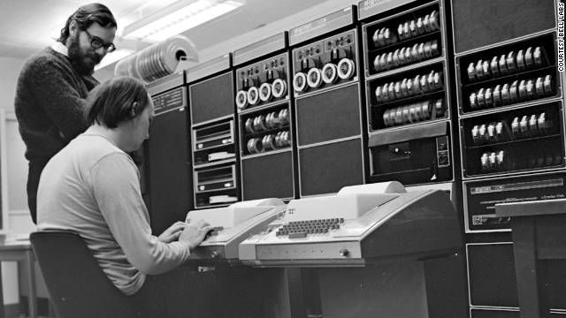 """Dennis Ritchie stands over Ken Thompson as he works on the PDP-11 (1972). They authored a computer language you may have heard of. It's called """"C""""."""