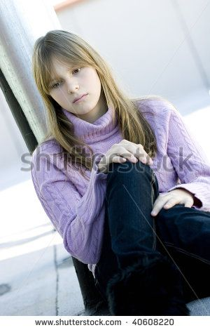 Young teenager girl with blond hair and bangs sitting with her knee bent in sad depressed expression