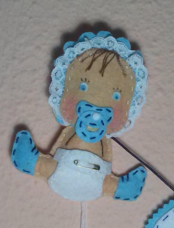 Detalle de bebé de fieltro con el nombre del peque en la ropita que lo acompaña, muy original para colgar en la habitación....