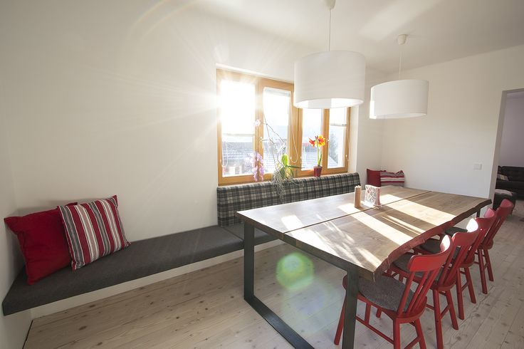 Fünf Meter lange raumlange Sitzbank aus unserer Tischlerei, tapeziert mit Steiner Loden. Massiver Eichentisch.
