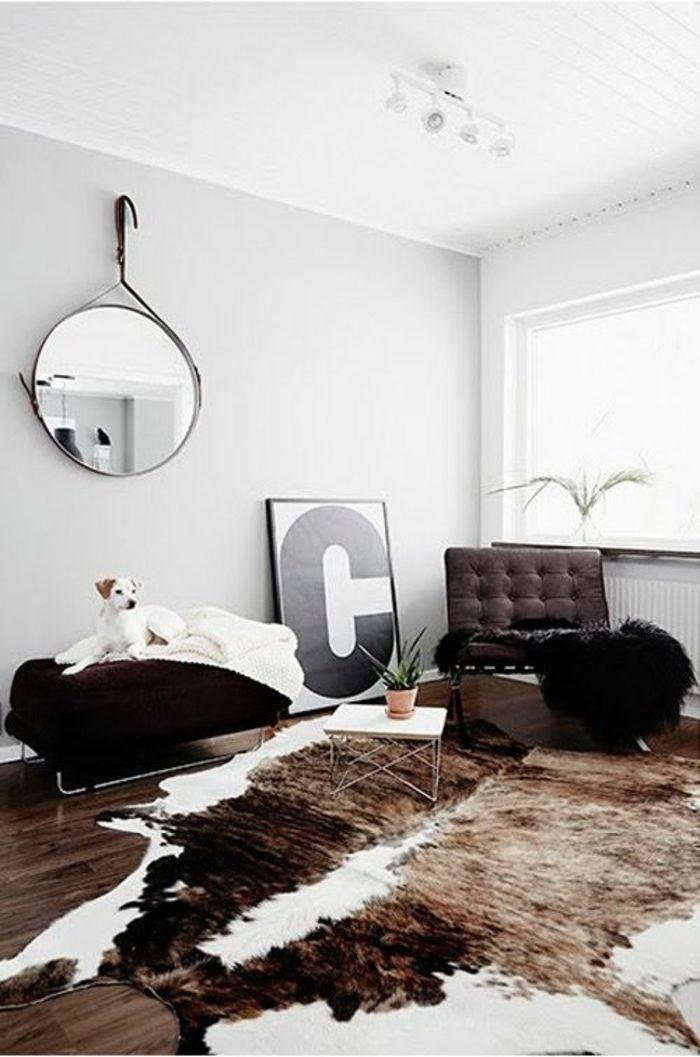 sol en parquet foncé, miroir décoratif sur le mur, plafond blanc, peau de bete sur le sol