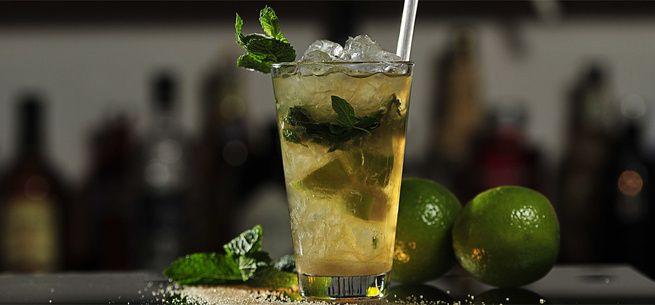 Rezept für Mojito: Minze zwischen den beiden Handinnenseiten anklatschen und mit Rum, Limettensaft, Rohrzucker und Soda ins Glas geben. Mit Würfeleis auffüllen und verrühren.