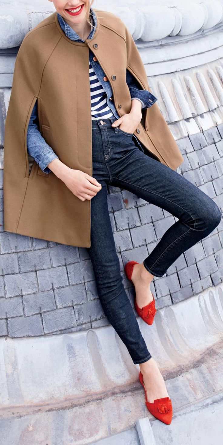 Tan/camel buttoned cape coat Bright red orange tassel flats Blue skinny jeans denim Chambray shirt striped shirt Winter layers/coat