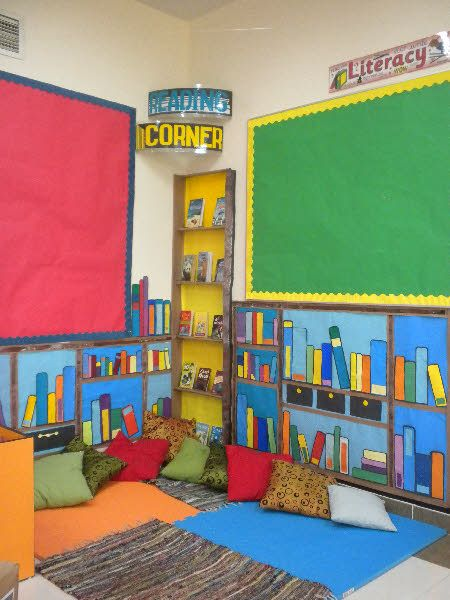 KS2 Reading Corner classroom display photo. I love the idea of putting fake books on the walls. You could even put your favorite authors or the books the kids will be reading that year.