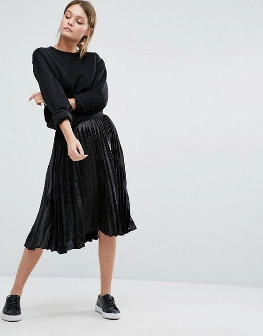 Pretty little black pleated skirt paired with trainers and xxl knit jumper