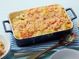 No. 48: Ina's Mac and Cheese : Ina's creamy macaroni and cheese is meant for a party. Gruyère cheese mixed with extra-sharp cheddar gives this dish grown-up flavor, while a topping of sliced tomatoes and breadcrumbs makes it extra special.
