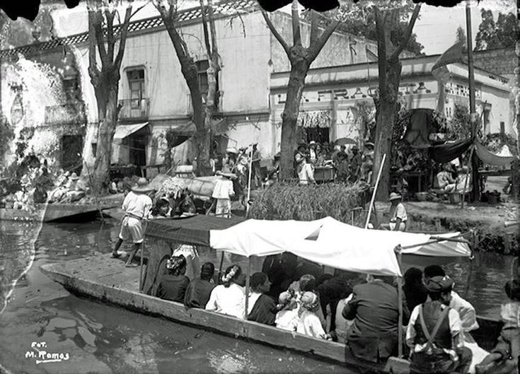 """Imagen del Canal de la Viga al cruce con la calle de Yunque, cerca del antiguo Puente de Jamaica, alrededor de 1910, durante las fiestas del Viernes de Dolores. Al fondo aparece la pulquería """"La Fragata"""", nombre que evoca l"""