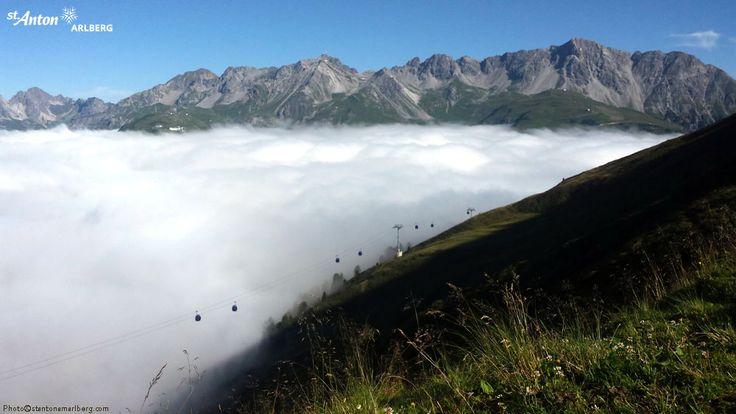 Alpenrosenweg in St. Anton am Arlberg.  Die beeindruckenden Gipfel der Lechtaler Alpen erheben sich aus dem Wolkenmeer in das die Gondeln der Rendelbahn eintauchen. Tirol | Austria