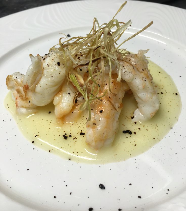 Scampi, potatoes cream, licorice powder and fried leeks