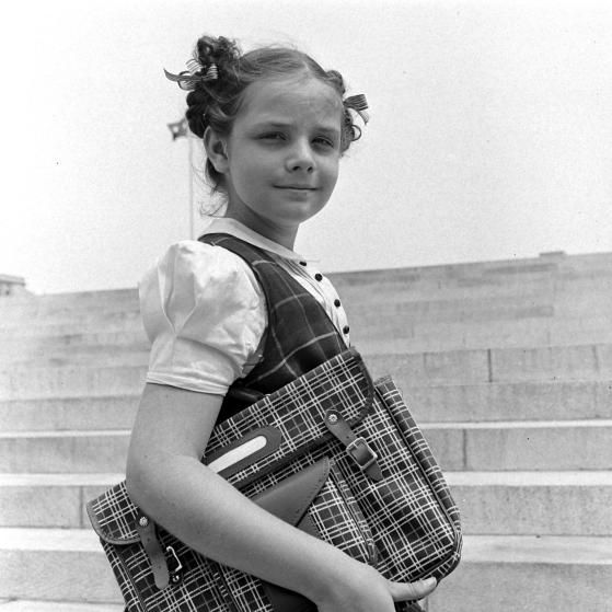 A young girl models a plaid jumper with a complementary plaid school bag. Back-to-school season of 1939.