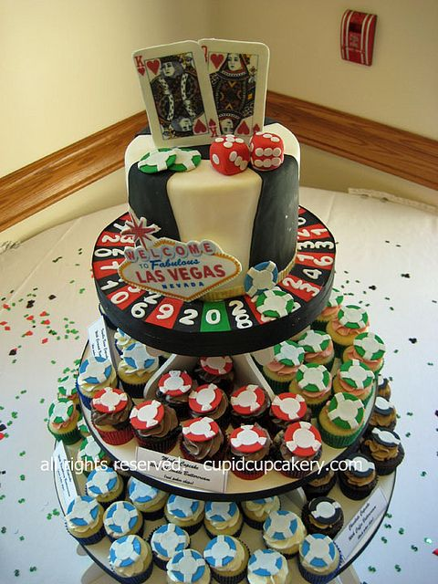 """Las Vegas Cake  Cupcakes by Cupid Cupcakery. I made this Vegas themed cake and cupcakes for a casual wedding reception after a couple got married in Las Vegas. Cake has playing cards (King and Queen of Hearts), poker chips in four colors, dice, an American roulette wheel and the famous """"Welcome to Fabulous Las Vegas"""" sign. Cupcakes were decorated with their own edible poker chips."""