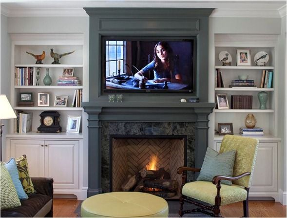 Built-in bookcases with fire place gas inserts | TV above mantle using up space efficiently.