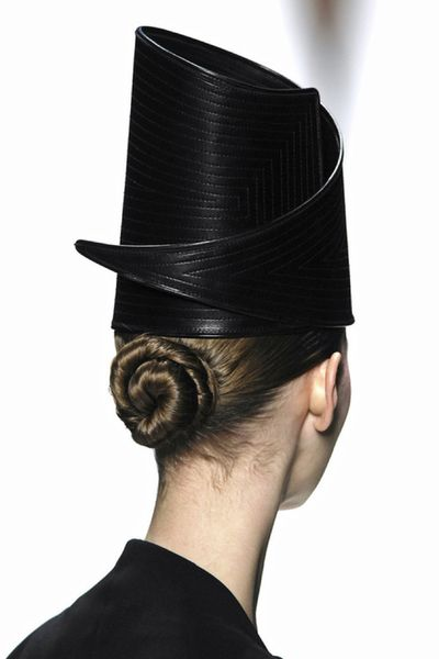 Low bun for a sculptural hat. I like how the wrap detail mirrors the wrapping on the hat.